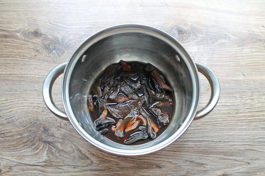 Переложите грибы и влейте воду после замачивания в кастрюлю, поставьте на средний огонь, доведите до кипения. Убавьте огонь, и варите грибы в течение 30-40 минут до готовности. Снимите с огня.