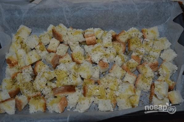 Порежьте хлеб, выложите на противень, полейте кусочки оливковым маслом, присыпьте солью, перцем и отправьте противень в горячую духовку на 15 минут при средней температуре. Помешивайте их каждые пять минут.