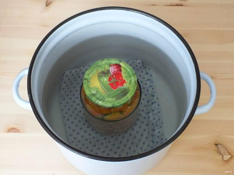 Возьмите глубокую, высокую кастрюлю. Застелите дно тканевой салфеткой, поставьте на нее банку, налейте в кастрюлю воды, чтобы она доходила чуть выше плечиков банки. Поставьте на сильный огонь. Стерилизуйте салат в течение 1 часа - для литровых банок,  35 минут - для банок объемом 0,5 литра, после закипания воды. После достаньте, закройте герметично крышками, переверните и охладите в таком виде.