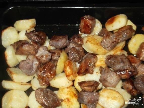 4.Картофель нарежьте кружочками. В противень положите картофель. Запекайте 20 минут, добавляя жир. Добавьте к картофелю мясо и перемешайте.