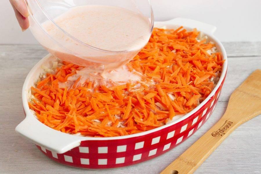 Морковь очистите, помойте, натрите на крупной терке и выложите поверх капусты. Подготовьте заливку: венчиком смешайте томатную пасту, сметану и воду. Посолите по вкусу и перелейте в форму. Поставьте запекаться на 50-55 минут при температуре 180 градусов.