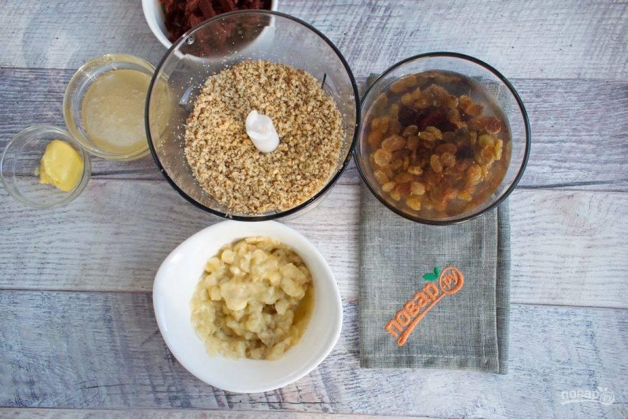 Цукаты, изюм и клюкву залейте горячей водой на 5 минут, слейте воду. Орехи измельчите с помощью блендера в мелкую крошку. Банан измельчите в пюре.