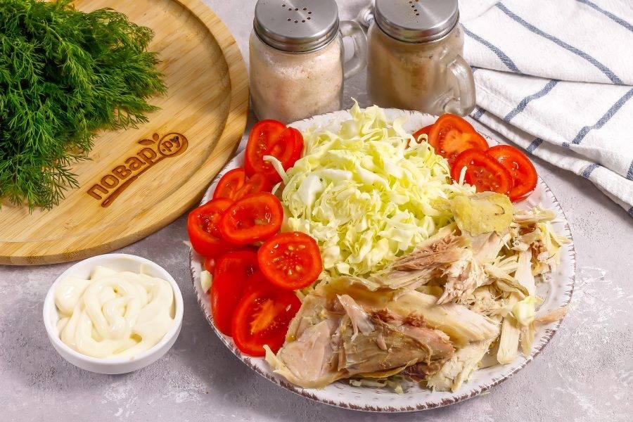 Отварную курицу руками или ножом разберите на волокна. Помидоры промойте в воде и вырежьте из них зеленые сердцевинки. Нарежьте ломтиками. Капусту мелко нашинкуйте. По желанию можете добавить картофель-фри или ломтики отварного картофеля, соленый огурец.