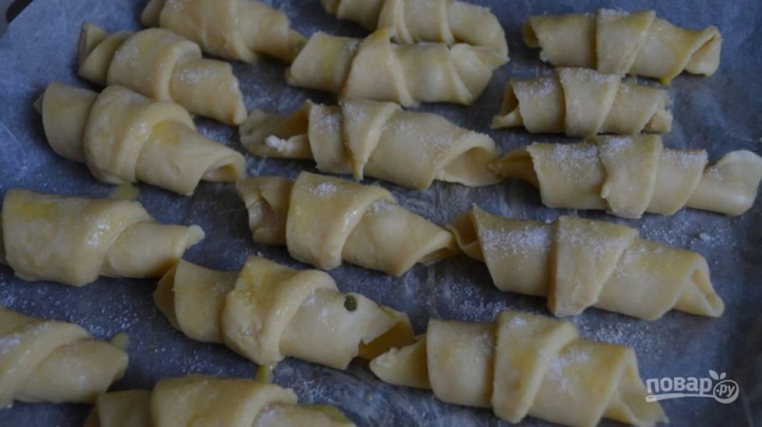 4.Начиная от широкой части скатайте рогалики, переложите их на противень с пергаментом, смазанный растительным маслом. Смажьте смесью яйца и сахара.
