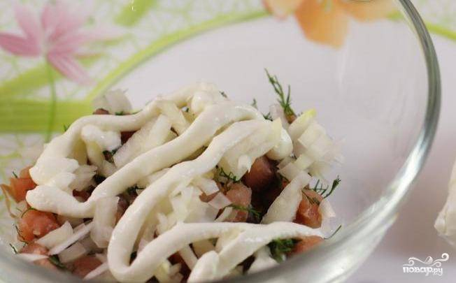 На дно салатницы уложите рыбу. Почистите и измельчите лук, уложите его следующим слоем. Смажьте майонезом.
