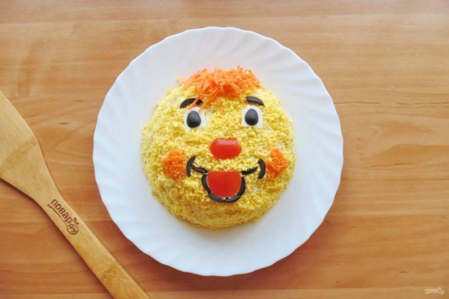 С помощью помидора, яичного белка, моркови и маслин оформите лицо колобка.