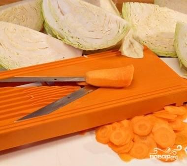 2. Капусту моем, снимаем у неё верхние листья, удаляем кочерыжку и разрезаем саму капусту на четыре части. Чистим и нарезаем кружочками морковь.