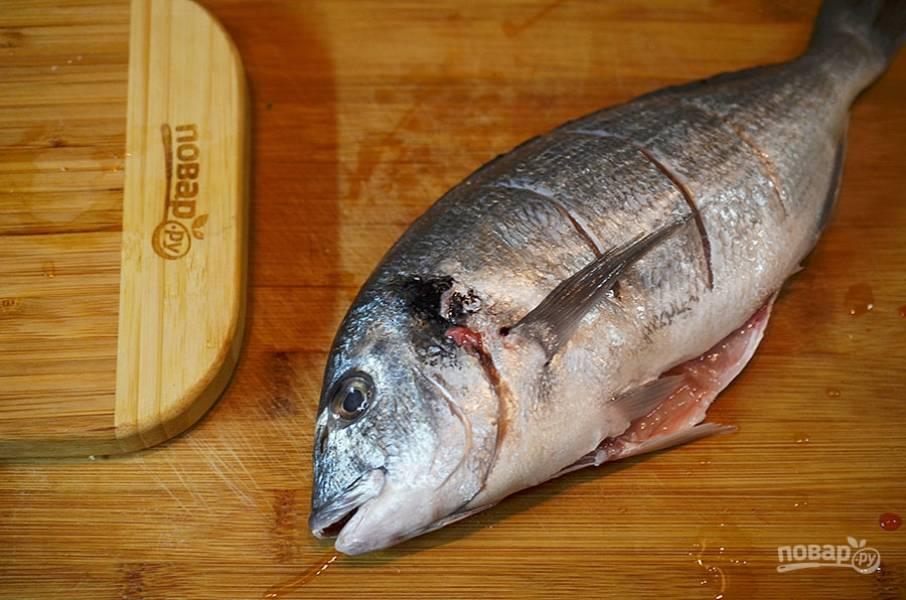 6. Рыбу выпотрошите, удалите жабры, сделайте поперечные надрезы.
