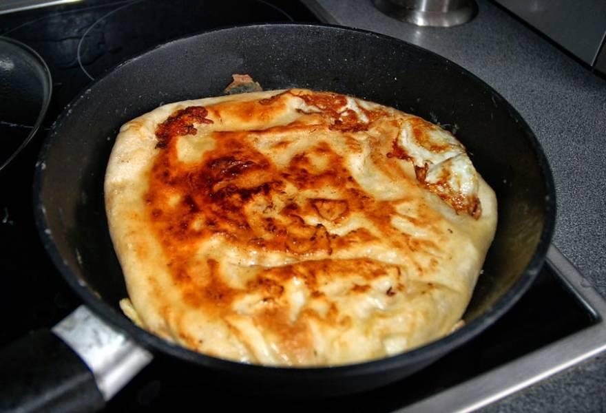 5. Когда низ подрумянится, аккуратно переверните лаваш на другую сторону. Сверху еще посыпьте горстью сыра. Оставьте лаваш на сковороде еще на 2-3 минуты.