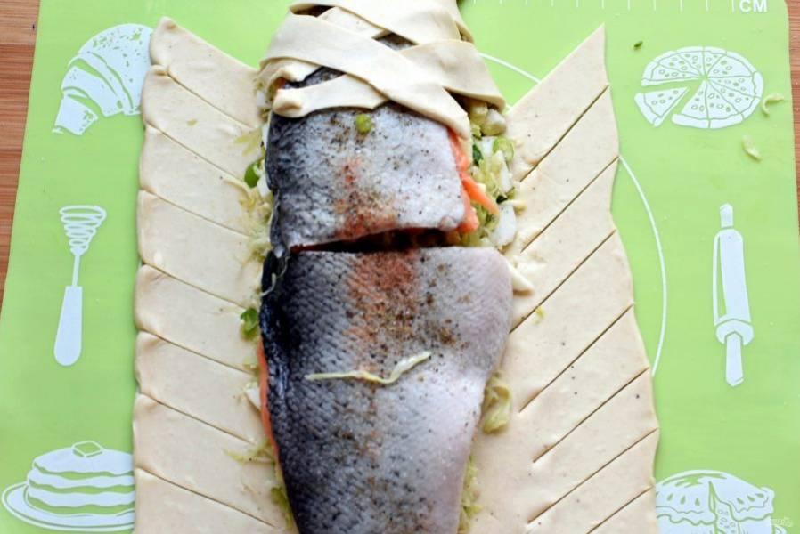 Тесто с боков нарежьте ровными неширокими полосками под углом в 45 градусов. Поочередно заворачивайте полоски на начинку, формируя плетенку.