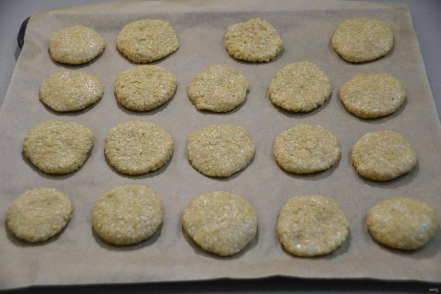 Отделите кусочек теста размером с грецкий орех. Сделайте из него лепешку и укладывайте на бумагу для выпечки, оставляя расстояние между печеньем.