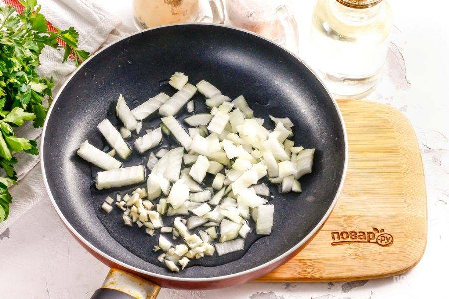 Очистите от шелухи репчатый лук и чеснок, промойте и разрежьте лук пополам. Нарежьте половину мелким кубиком, а чесночные зубчики измельчите. Прогрейте на сковороде растительное масло — его можно заменить сливочным топленым.