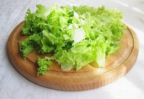 Тщательно промоем листья салата, обсушим и порвем его на кусочки.