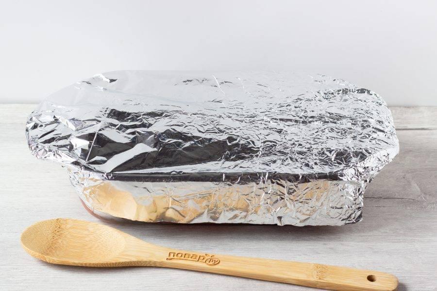 Закройте форму фольгой и поставьте в разогретую до 180 градусов духовку на 1 час 20 минут. По истечении времени выключите духовой шкаф, а мясо оставьте внутри ещё на 40-60 минут.