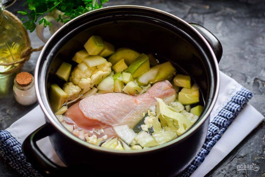 Влейте в кастрюлю воду, добавьте курицу. Варите суп 25-30 минут. Спустя время курицу извлеките, отделите мясо от кости, верните мясо в кастрюлю.