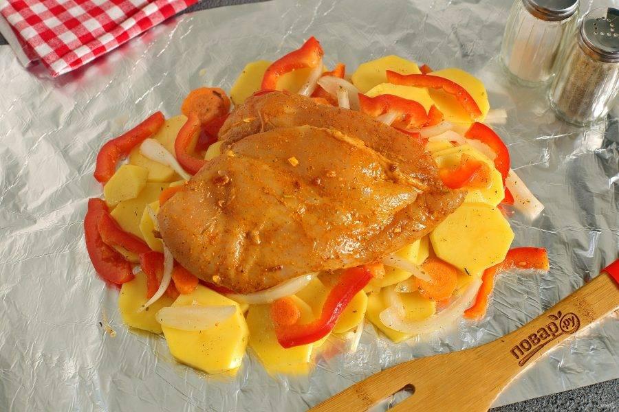 Выложите овощи на кусок фольги. Поверх овощей выложите куриную грудку. Плотно укутайте курочку с овощами фольгой, чтобы сок не вытекал на противень и запекайте в духовке при температуре 180 градусов 30-40 минут.