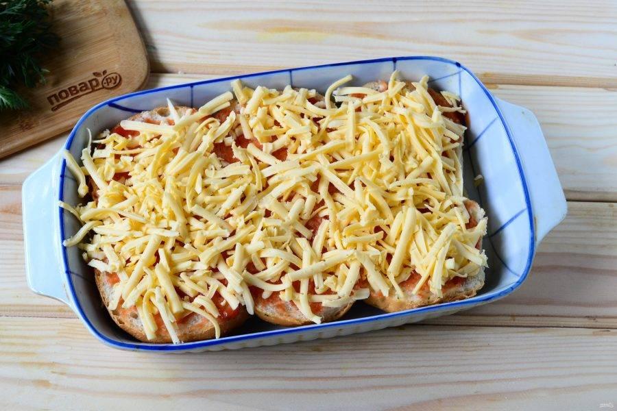 Сыр натрите на крупной терке, оставив примерно 1/4 часть. Половиной натертого сыра присыпьте булочки.