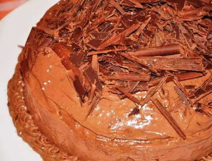 Поставьте торт в холодильник на 4-5 часов, затем посыпьте шоколадной стружкой, какао и украсьте ягодами малины.