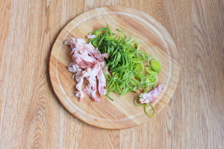 Бекон и зелень лука-порея нарежьте соломкой.