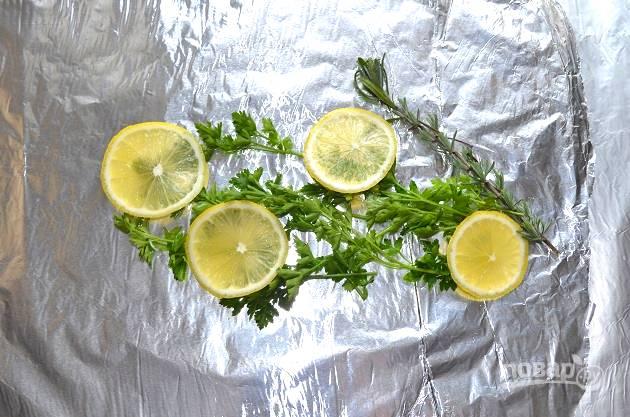 На лист фольги выложите промытую и обсушенную зелень. У меня пучок петрушки и веточка розмарина. Сверху выложите несколько ломтиков лимона.