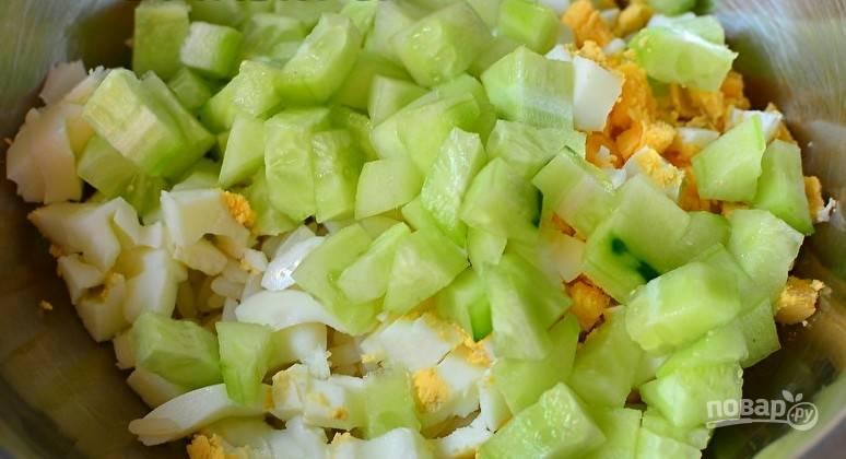 В салатницу к рису и яйцам добавьте нарезанный огурец.