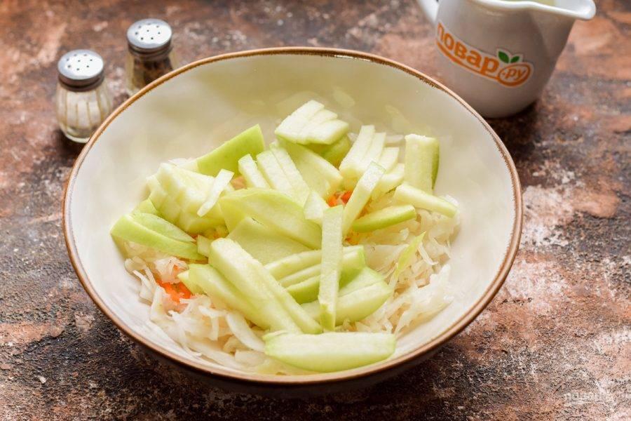 Яблоко очистите и удалите серединку. Нарежьте яблоко небольшими полосками. Переложите яблоко в миску к капусте.