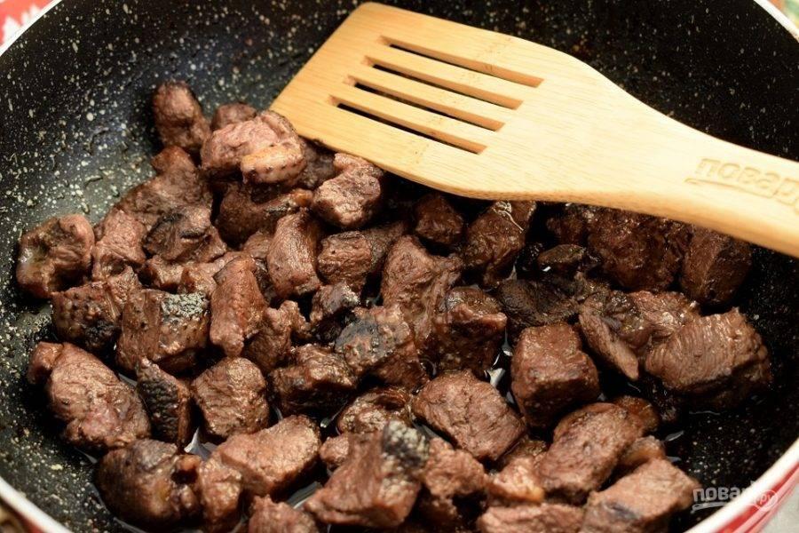 Мясо нарежьте на кусочки по 2 см. Разогрейте масло на сковороде, на сильном огне обжарьте мясо до румяной корочки с двух сторон.