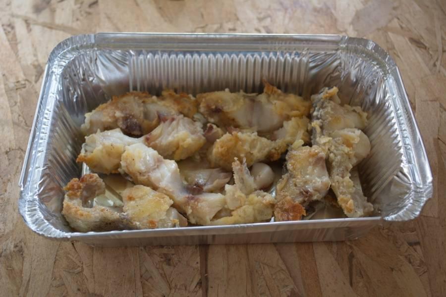 Обжаренную рыбку перенесите на разделочную доску. Двумя вилками удалите центральную кость. Филе рыбы выложите в смазанный маслом лоток для запекания.