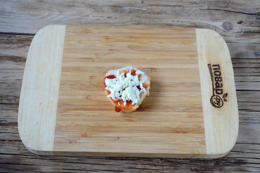 Первый кусочек смажьте томатным соусом для пиццы, сверху положите щепотку натертой на крупной терке моцареллы.
