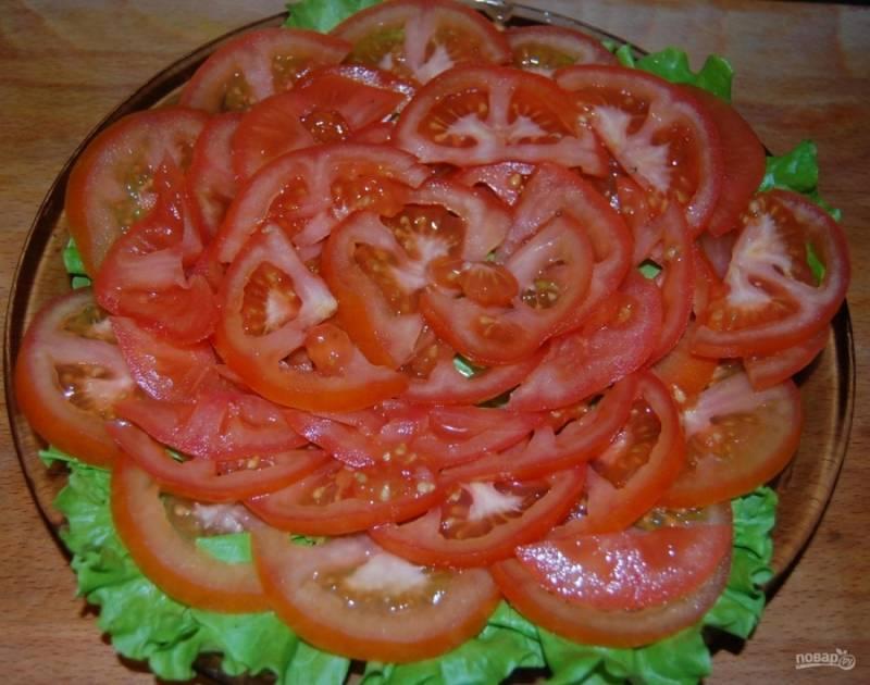 4.Тем временем мою и нарезаю тонкими кольцами спелые помидоры. Укладываю их на салатные листья.