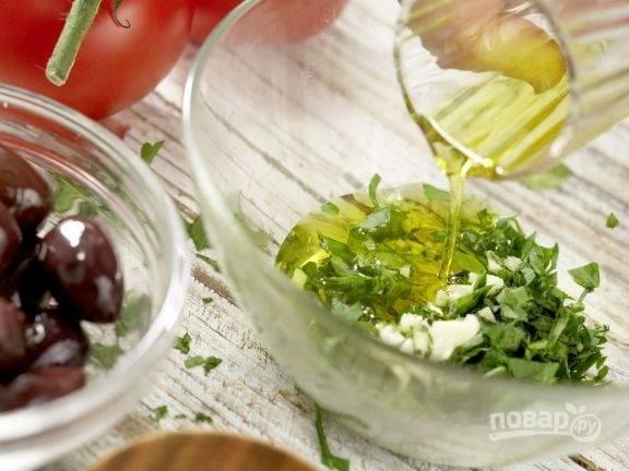 Вначале сделайте маринад для кальмара. Измельчите петрушку и чеснок. Залейте их оливковым маслом.
