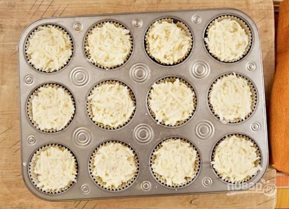 1.Очистите картофель и натрите его на крупной терке, смешайте его с растительным маслом, солью и перцем. В формы для выпечки кексов выложите фольгу (специальные формочки). Распределите картофель между всеми формочками.