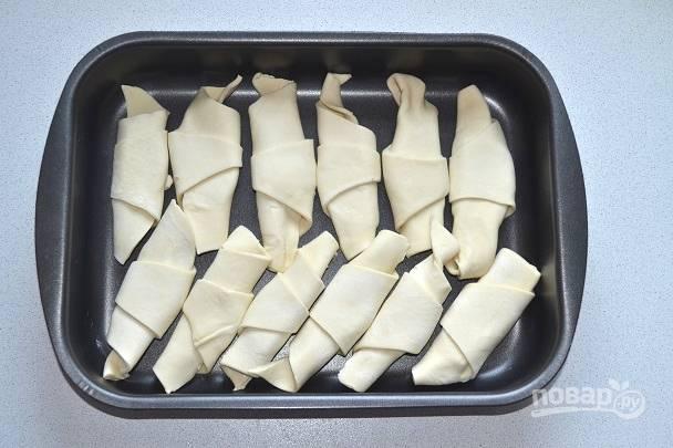 Выложите готовые слойки в форму для запекания.