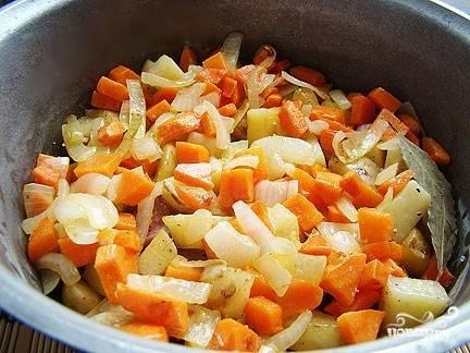 8.Когда свиные ребрышки будут уже почти готовы, выкладываем к ним в казан все овощи. Посыпаем соль, перцем и другими приправами. Можно добавить лавровый листик. Вместо соли можно использовать соевый соус. Тщательно все перемешиваем и тушим до готовности, периодически перемешивая овощи с ребрышками лопаткой.