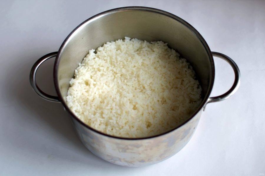 Начните с варки риса. Промойте рис хорошенько и опустите в кастрюлю с отмерянным кипятком. Варите на среднем огне до впитывания воды. Затем проложите под крышку салфетку и готовьте еще 5 минут на минимальном нагреве. Дайте остыть до теплого состояния. Смешайте рисовый уксус с солью и сахаром до полного растворения. Влейте смесь в кастрюлю с рисом и рубящими движениями силиконовой лопатки перемешайте.
