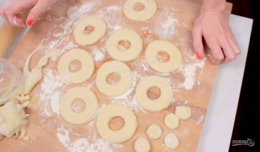 4. Далее тесто раскатайте в пласт толщиной 1,5-2 см, но не давите его. С помощью формочек вырежьте кружочки в форме пончиков. Оставьте их на столе на полчаса, чтобы пончики еще поднялись.