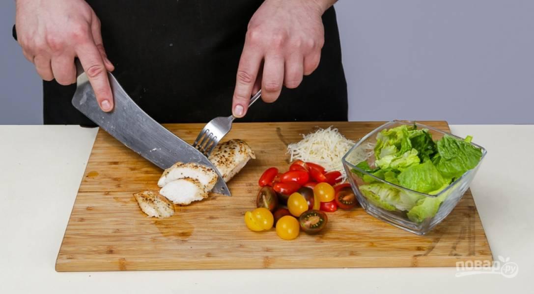 Сыр натрите на мелкой терке, грудку нарежьте медальонами, а помидоры — попалам, салат порвите на кусочки.