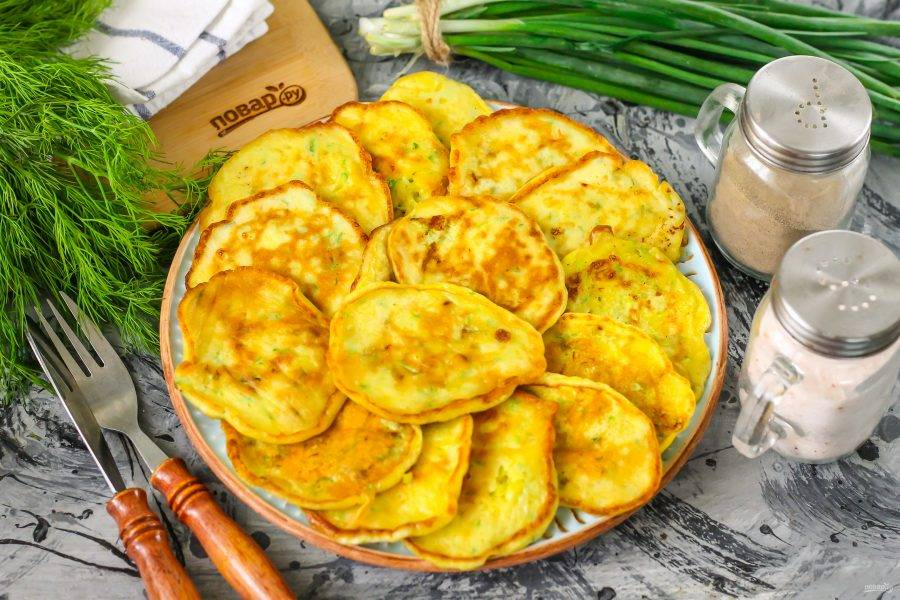 Подайте кабачковые оладьи с фетой к столу теплыми, чтобы сыр в тесте приятно тянулся. Не забудьте про сметану, сливки или чесночный соус.