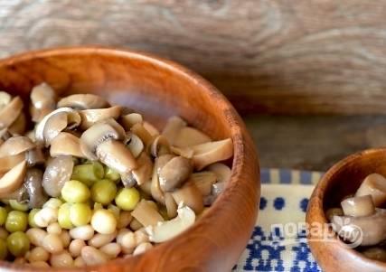 Откройте банку с мариноваными грибами. Прекрасно подойдут опята или лисички, также любые другие мелкие грибы. Добавьте немного грибов к остальным ингредиентам.