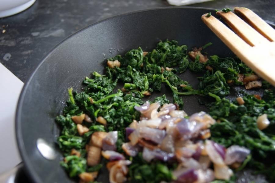 3. На сковороду отправить небольшой кусочек сливочного масла и растопить его. Положить шпинат и обжарить немного. Затем добавить лук и измельченные грибы. Немного подсолить и поперчить все по вкусу.