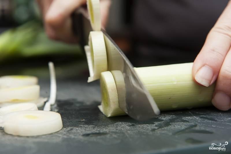 Нарежьте перец и лук порей. Промойте картофель.