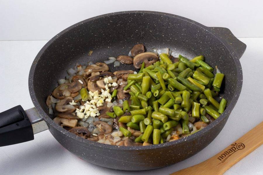 Затем добавьте мелко рубленный чеснок и заранее сваренную фасоль. Жарьте ещё 3-4 минуты помешивая.