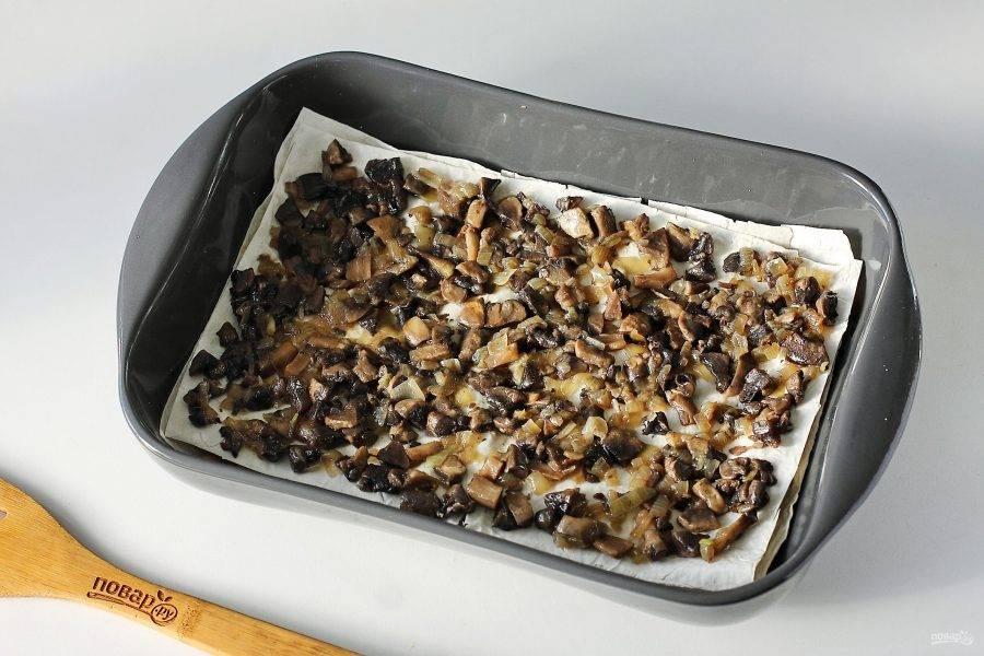 Накройте начинку вторым листом и сверху выложите обжаренные с луком грибы.