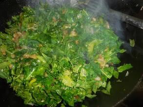 2. На том же масле, что осталось, тушим помытый и обсушенный шпинат с кинзой, луком и базиликом. Добавьте немного воды, специй, тушите до готовности.