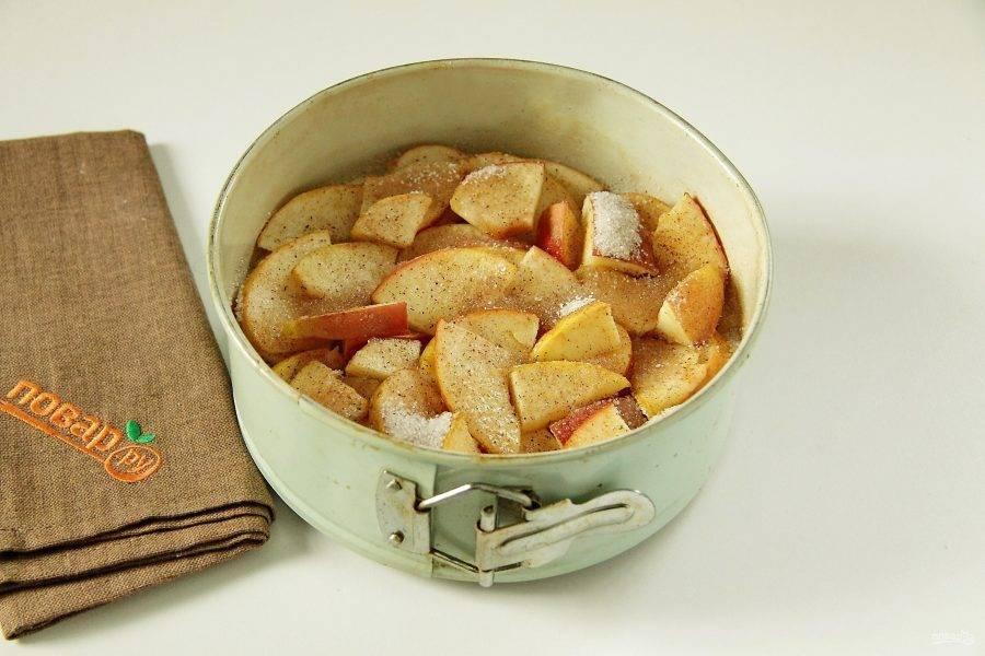 7. Нарежьте произвольно яблоки и разложите сверху. Смешайте оставшийся сахар и специи. Посыпьте равномерно яблоки.