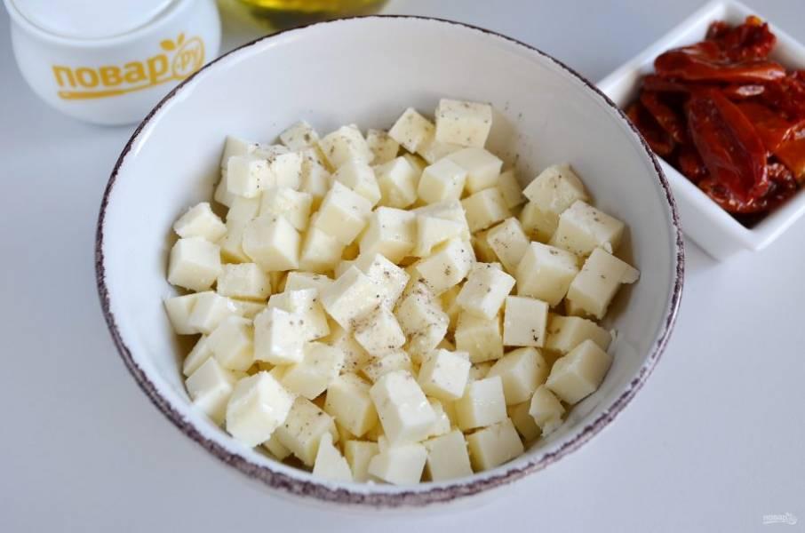 6. Сыр порежьте кубиками, добавьте столовую ложку или две оливкового масла, перца черного. Осторожно перемешайте.