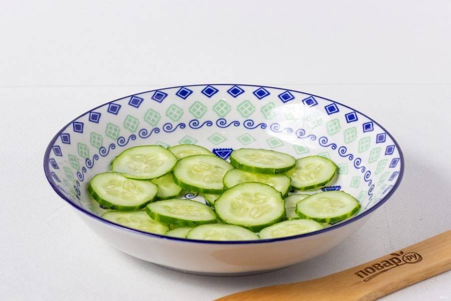 Овощи будем выкладывать слоями, поэтому подбирайте подходящее блюдо. Первый –слой огурцов, нарезанных кружочками.