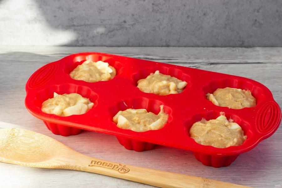 Добавьте яблоки в тесто, перемешайте. Разложите тесто в порционные формы. Силиконовые я ничем не смазываю, металлические можно смазать растительным маслом.