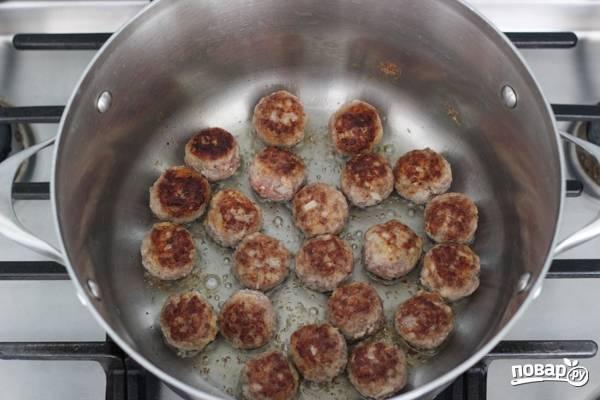 4. В кастрюле или сотейнике разогрейте немного растительного масла. Выложите фрикадельки небольшими порциями и обжарьте на сильном огне до румяности.