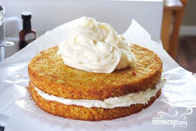 7. Выложить один пирог на тарелку, смазать сливочной глазурью, накрыть сверху вторым пирогом и снова смазать глазурью. Охладить, нарезать на куски и подавать.